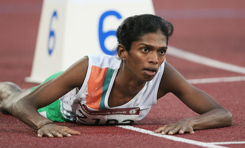 In this file picture taken December 9, 2006, India's Santhi Soundarajan lies on the track after edging out Kazakhstan's Viktoriya Yalovtseva for second place in the women's 800m final on the second day of the athletics competition for the 15th Asian Games at Khalifa Stadium in Doha. Indian athlete Santhi Soundarajan, who was stripped of her Asian Games silver medal for what was branded a failed gender test, hopes South African Caster Semenya will not suffer the same fate. AFP PHOTO/MARWAN NAAMANI/FILES (Photo by MARWAN NAAMANI / AFP FILES / AFP)