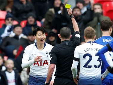Tottenham's Son Heung-min is shown a yellow card by referee Michael Oliver. Reuters