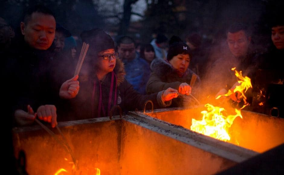 Hundreds lined up outside famous temples to burn the first joss sticks of the year, expecting it to bring them good luck. AP