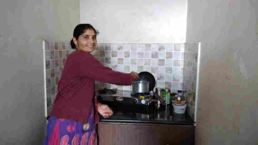Santoshi works in her small kitchen with a smile on her face, thankful that she does not have to fetch water everyday. Varsha Singh