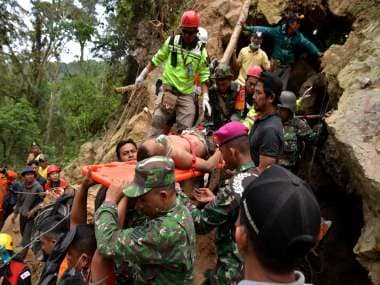 Eight killed in Indonesia gold mine collapse; rescue teams deploy excavator to search for three dozen still feared trapped