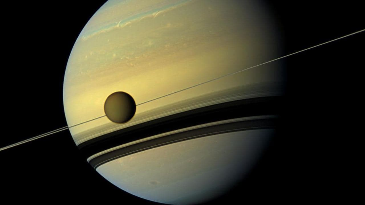Saturn and its moon Titan that is now drifitng away from the planet