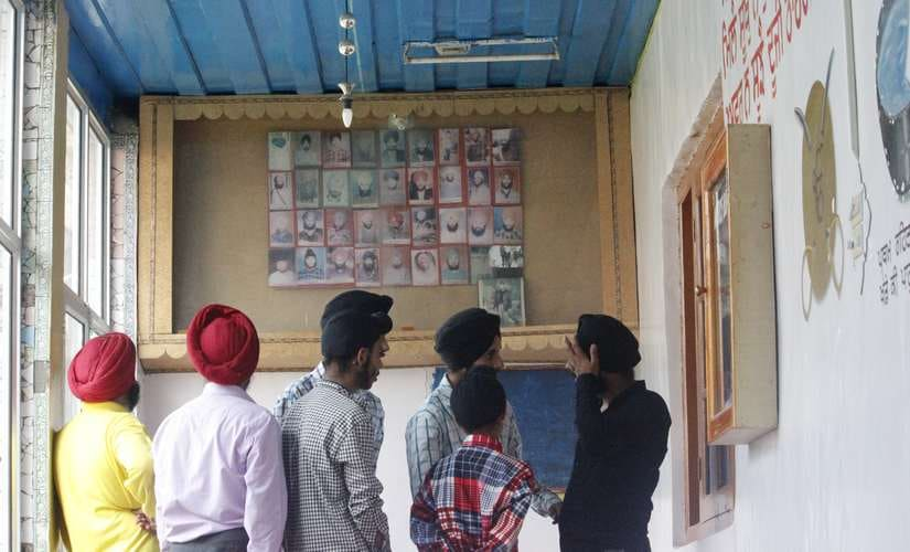 The wall in the background contains pictures of those killed in Chittisinghpora massacre Image courtesy: Aamir Ali Bhat