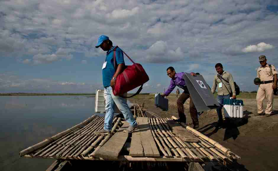 Election officials and paramilitary soldiers with election materials board on a country boat to cross the river Brahmaputra on the eve of first phase of general election in Majuli, Assam. AP