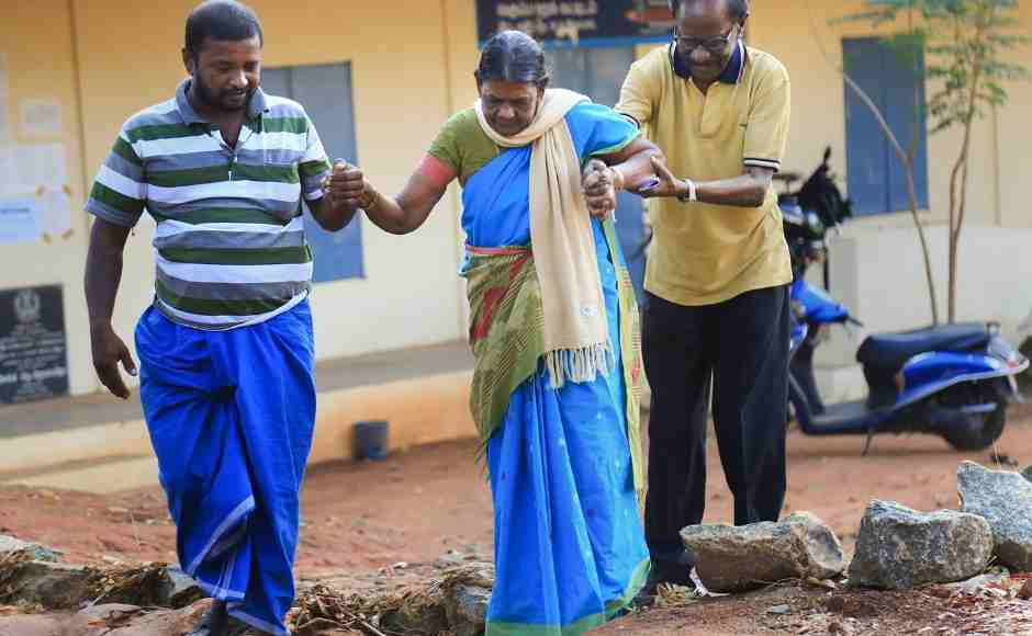 An elderly voter is assisted as she arrives to cast vote at a polling station in Nagercoil in Kanyakumari. PTI
