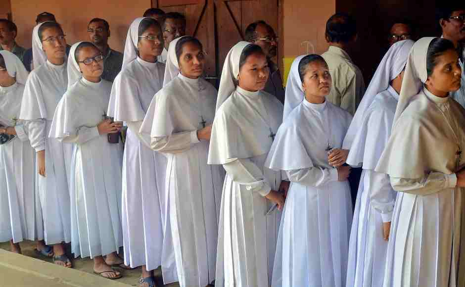 Christian nuns wait in a queue to cast their votes at a polling station in Guwahati. PTI