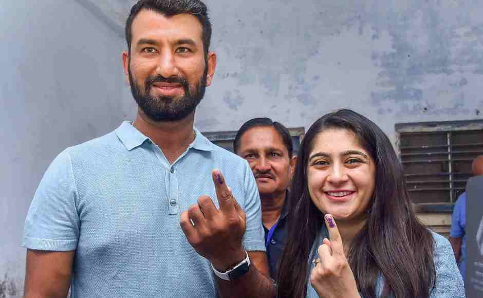 Indian cricketer Cheteshwer Pujara and his wife Puja Pabari show their inked marked fingers at a polling station in Rajkot. PTI