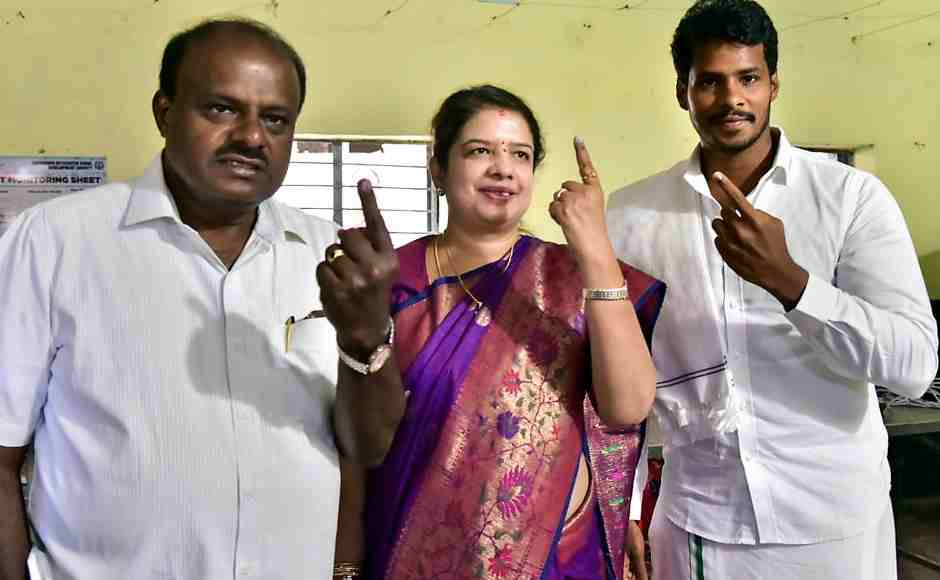 Karnataka chief minister HD Kumaraswamy along with wife Anitha Kumaraswamy (C) and son Nikhil Gowda (R) show their finger marked with indelible ink after casting vote at a polling station at Kethiganahalli in Ramanagara district. PTI