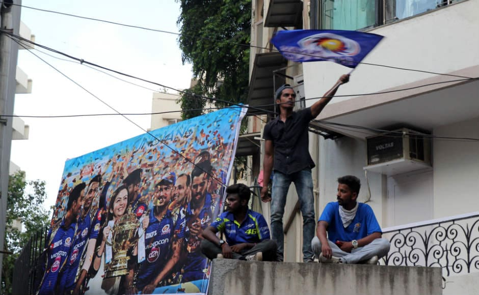 A fan waves the Mumbai Indians flag shortly before the Mumbai Indians open-top bus parade. Sachin Gokhale