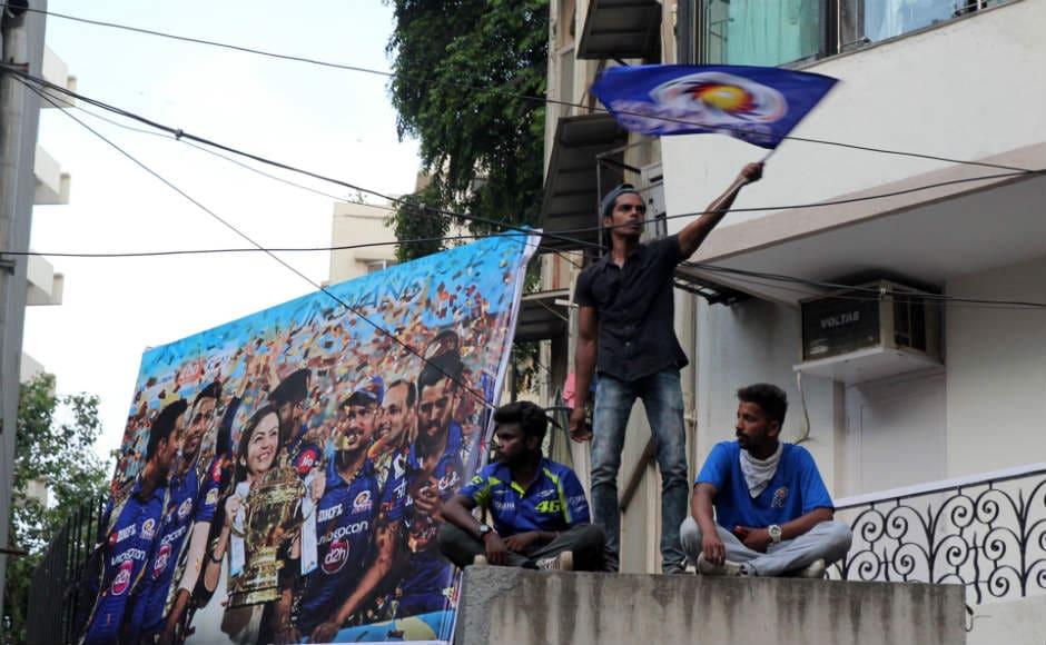 A fan waves the Mumbai Indians flag shortly before the Mumbai Indians open bus parade. Sachin Gokhale