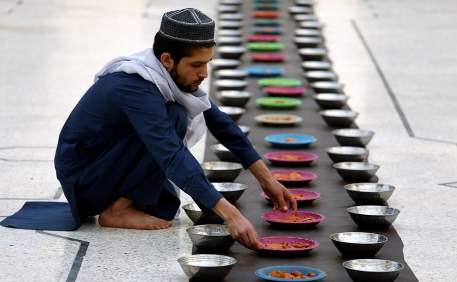 A man arranges food plates for people in Peshawar, Pakistan. During Ramadan, Muslims fast from dawn to sunset, eating only once the sun has gone down, spending the day in prayer and reflection. Reuters/Fayaz Aziz.
