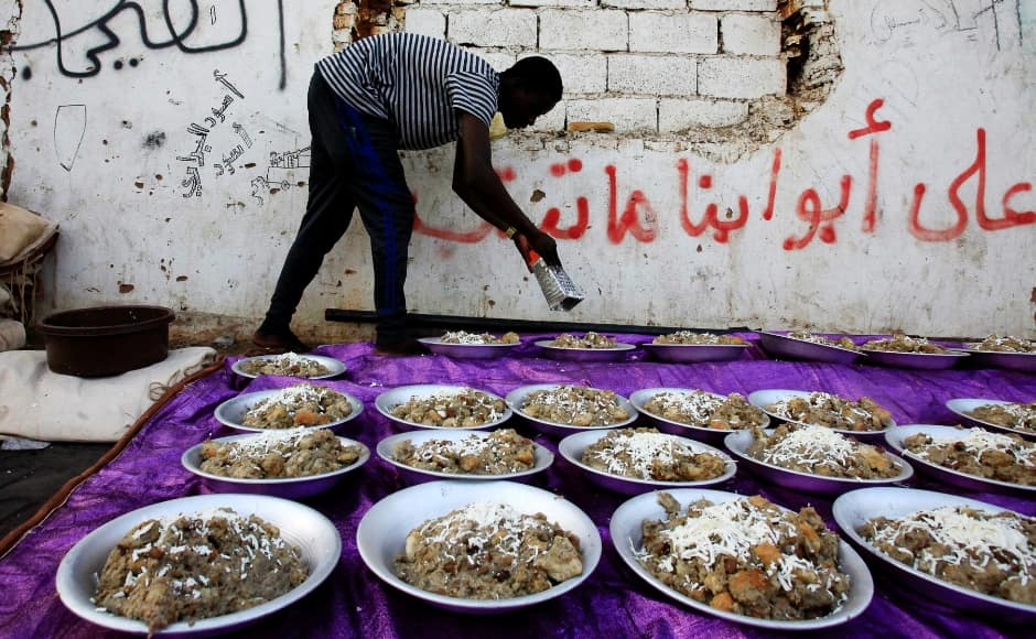 A Sudanese protester serves Iftar as they prepare to break their fast during the first day of Ramadan, in front of the Defence Ministry compound in Khartoum, Sudan. <em>Iftar</em> or <em>Fatoor</em> is the meal that Muslims eat in the evening, to end the day's fasting, at sunset. Reuters/Mohamed Nureldin Abdallah.