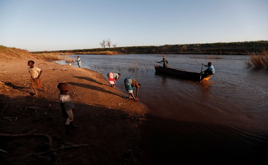Jofresse'sfather Joao, who works on a water taxi, returns from the opposite shore as Jofresse, her mother Ester Thoma, and other survivors wash themselves in the water of the Muda River. Reuters/Zohra Bensemra.