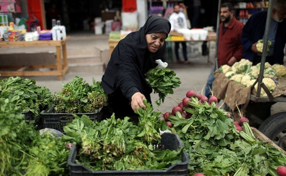 A Palestinian woman sells vegetables on the first day of Ramadan, in the southern Gaza Strip. Reuters/Ibraheem Abu Mustafa.