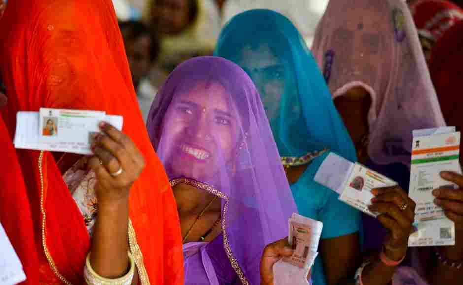 Women in Nagaur district showed their ID cards as they waited to cast their votes at a polling station. PTI