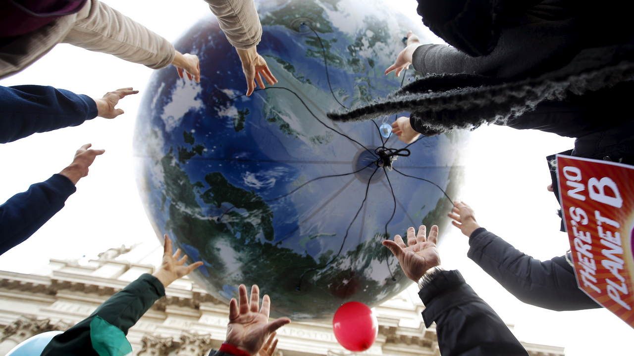 Protesters throw up a globe-shaped balloon during a rally held the day before the start of the COP21 summit. image credit:Reuters