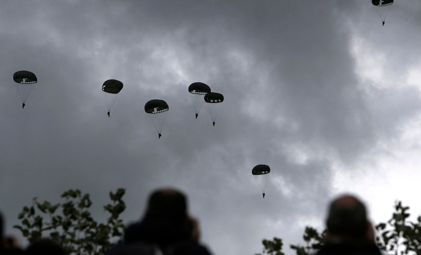 Spectators watch parachutists jumping just as soldiers did 75 years ago on D-Day. C-47 transport planes in World War II colors dropped sticks of jumpers with round canopies reminiscent of those used by airborne forces in 1944. AP