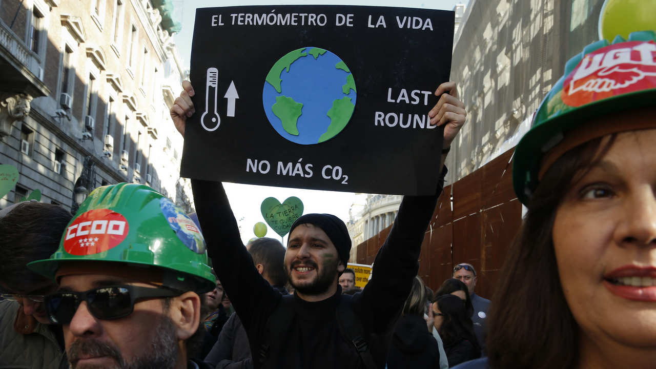 A protester holds up a placard as he demonstrates during a rally held the day before the start of the Paris Climate Change Summit in Madrid, Spain, November 29, 2015. The placard reads: