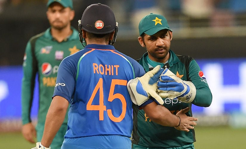 Pakistan's captain Sarfraz Ahmed (R) and Indian team captain Rohit Sharma (L) leave the field after India won by 9 wickets during the one day international (ODI) Asia Cup cricket match between Pakistan and India at the Dubai International Cricket Stadium in Dubai on September 23, 2018. (Photo by ISHARA S. KODIKARA / AFP)
