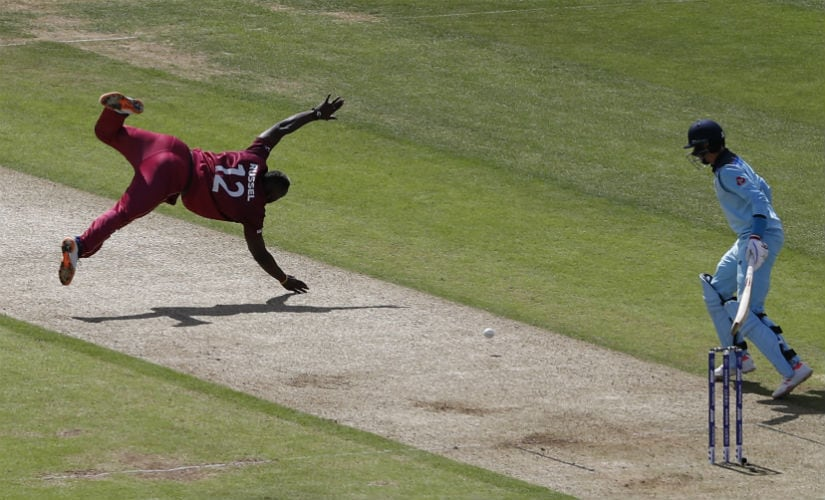 West Indies' Andre Russell (L) is watched by England's Joe Root as he attempts to field a ball off his own bowling during the 2019 Cricket World Cup group stage match between England and West Indies . AFP