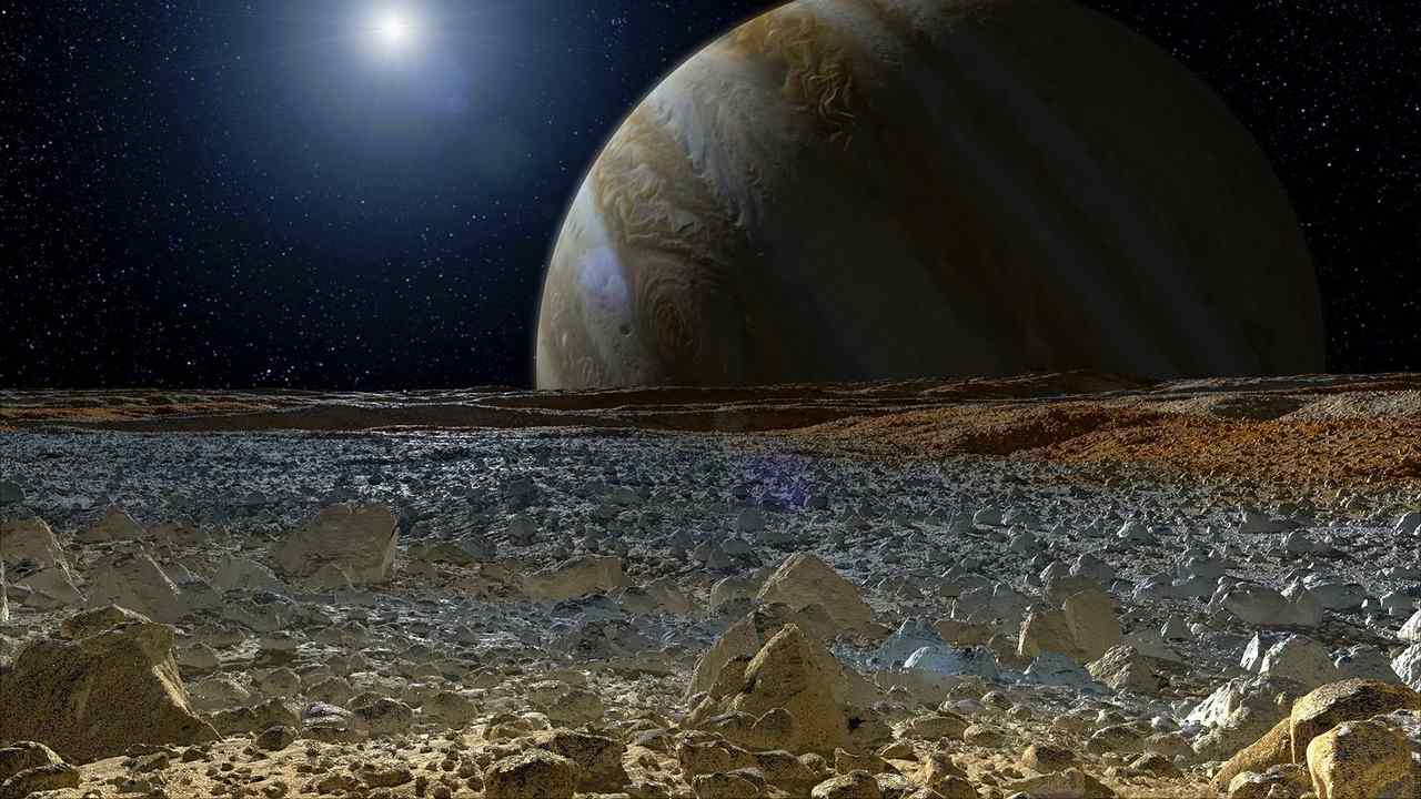 This artist's concept shows a simulated view from the surface of Jupiter's moon Europa. Europa's potentially rough, icy surface, tinged with reddish areas that scientists hope to learn more about. Image courtesy: NASA/JPL