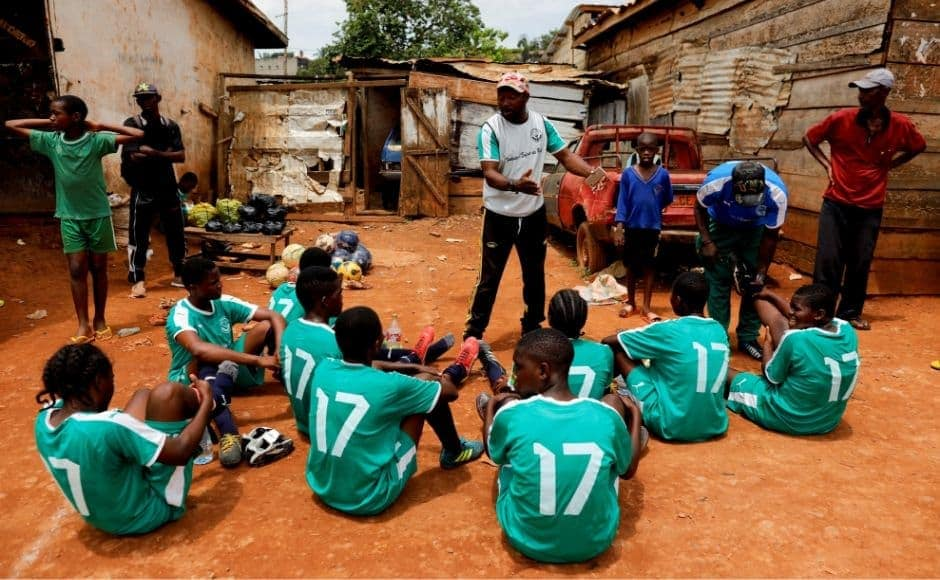 Coach Emmanuel Biolo talks to the girls during half-time at the Rails Foot Academy. The training centre gets its name from the train tracks surrounding the football field that also function as makeshift stands for spectators. Reuters/ Zohra Bensemra