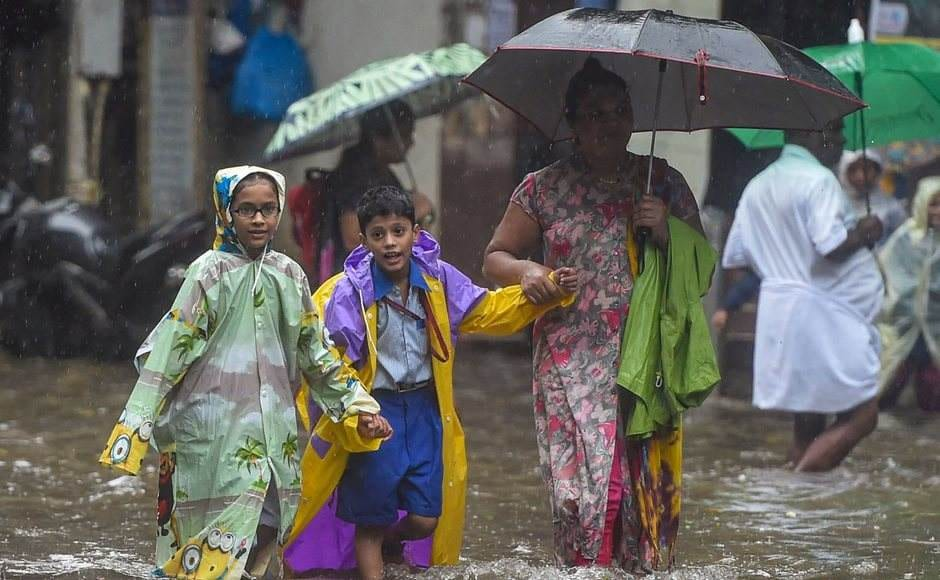 After a break of few days, heavy rains returned to Mumbai and its neighbouring areas on Monday morning, affecting road and rail traffic and briefly disrupting operations at the city airport. School children wade through a waterlogged street, following heavy monsoon rain in Mumbai. PTI