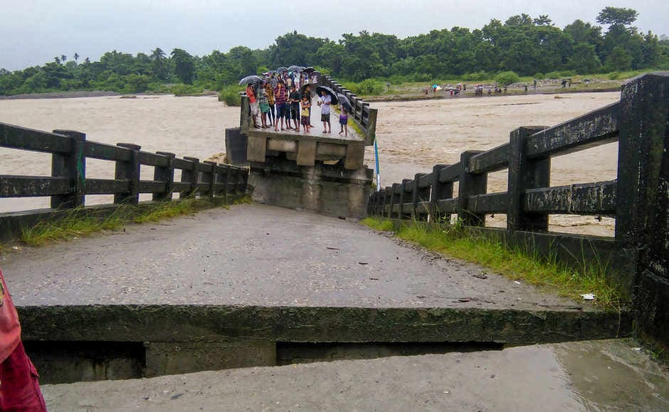 Villagers look on at a bridge which collapsed following incessant rainfall in their inundated village near Sujanghat, in Baksa district of Assam. PTI