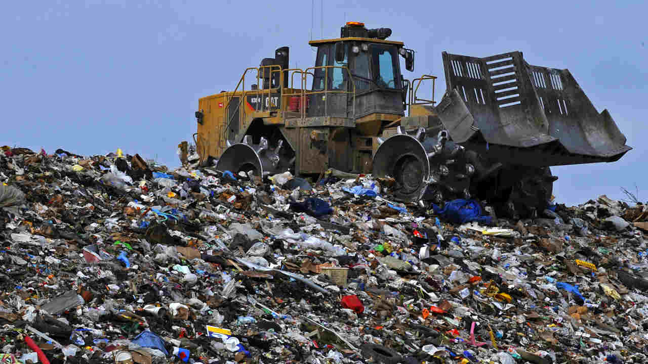 An excavator crushes trash at the Anchorage Landfill, Aug. 21. Image credit: U.S. Air Force photo/Tech. Sgt. Brian Ferguson