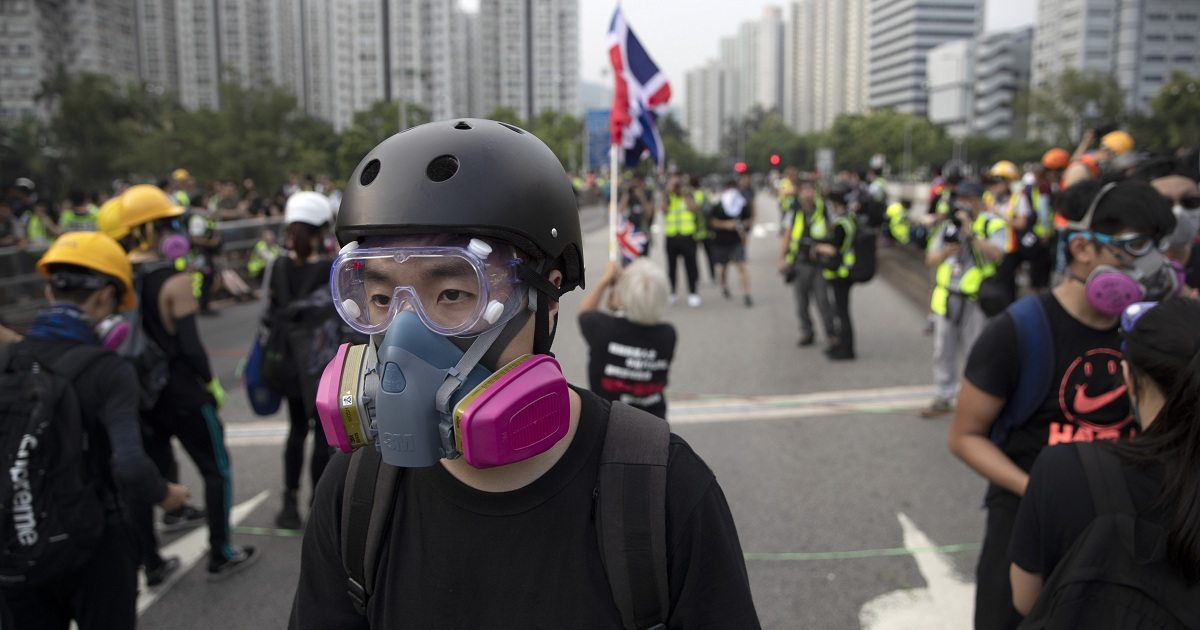"In this Aug. 16, 2019, photo, Wayne, a 33-year-old self-described ""front line"" protester, stands along with other demonstrators in Tai Po, on Hong Kong's outskirts. Hong Kong's protest movement has reached a moment of reckoning after protesters occupying the airport held two mainland Chinese men captive, and pro-democracy lawmakers and fellow demonstrators question whether the whole operation has gone too far. (AP Photo/Vincent Thian)"
