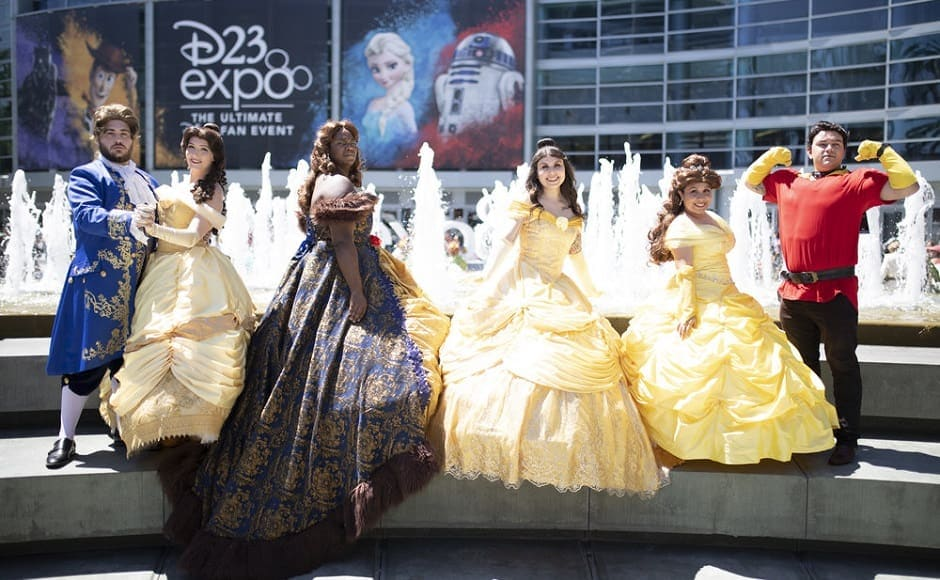 Fans posing as Belle from Beauty and the Beast in her iconic golden ball gown | The Walt Disney Company