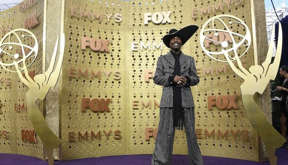 Billy Porter wears a Michael Kors Collection striped suit with a dramatic hat | Getty Images