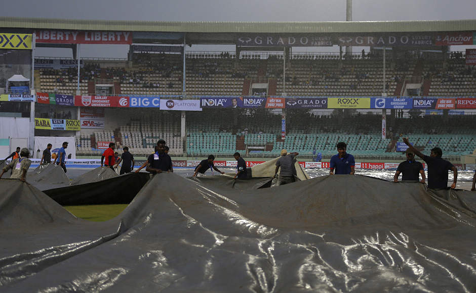 Covers are brought onto the ground after heavy rain forced the players off the field. The rain made it's appearance by tea time and the post-tea session was completely washed out. AP
