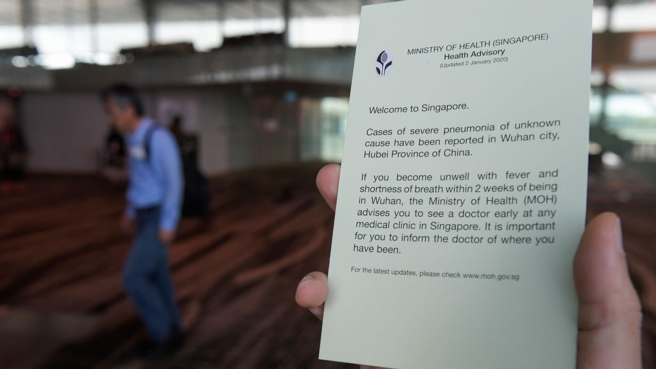 An airport staff holds health advisory cards for passengers at Changi International airport in Singapore on January 22, 2020 as authorities increased measure against coronavirus. - A new virus that has killed nine people, infected hundreds and already reached the United States could mutate and spread, China warned January 22, as authorities scrambled to contain the disease during the Lunar New Year travel season. (Photo by ROSLAN RAHMAN / AFP) (Photo by ROSLAN RAHMAN/AFP via Getty Images)