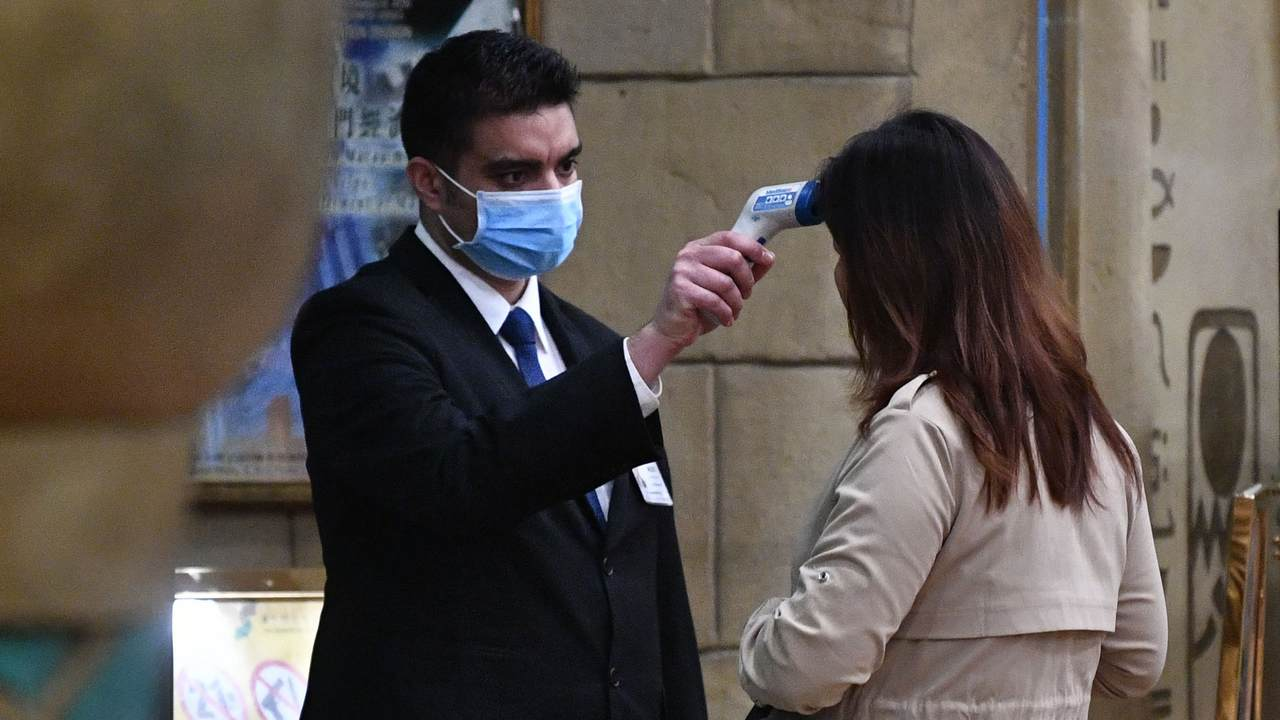 A staff member checks the temperature of a guest entering the casino of the New Orient Landmark hotel in Macau on January 22, 2020, after the former Portuguese colony reported its first case of the new SARS-like virus that originated from Wuhan in China. - Macau on January 22 reported its first confirmed case of the new SARS-like coronavirus as authorities announced all staff in the city's bustling casinos had been ordered to wear face masks. (Photo by Anthony WALLACE / AFP) / The erroneous mention[s] appearing in the metadata of this photo by Anthony WALLACE has been modified in AFP systems in the following manner: [entering the casino of the New Orient Landmark hotel] instead of [entering the New Orient Landmark hotel]. Please immediately remove the erroneous mention[s] from all your online services and delete it (them) from your servers. If you have been authorized by AFP to distribute it (them) to third parties, please ensure that the same actions are carried out by them. Failure to promptly comply with these instructions will entail liability on your part for any continued or post notification usage. Therefore we thank you very much for all your attention and prompt action. We are sorry for the inconvenience this notification may cause and remain at your disposal for any further information you may require. (Photo by ANTHONY WALLACE/AFP via Getty Images)