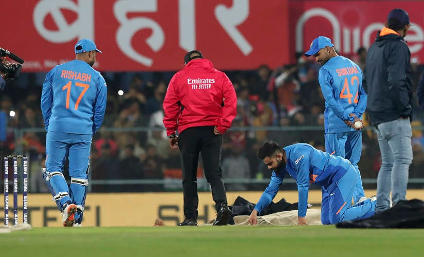 Indian captain Virat Kohli, third from right, inspect the pitch after the rain during the first Twenty20 cricket match between India and Sri Lanka in Gauhati, India, Sunday, Jan. 5, 2020. The match delayed for the rain. (AP Photo/Anupam Nath)