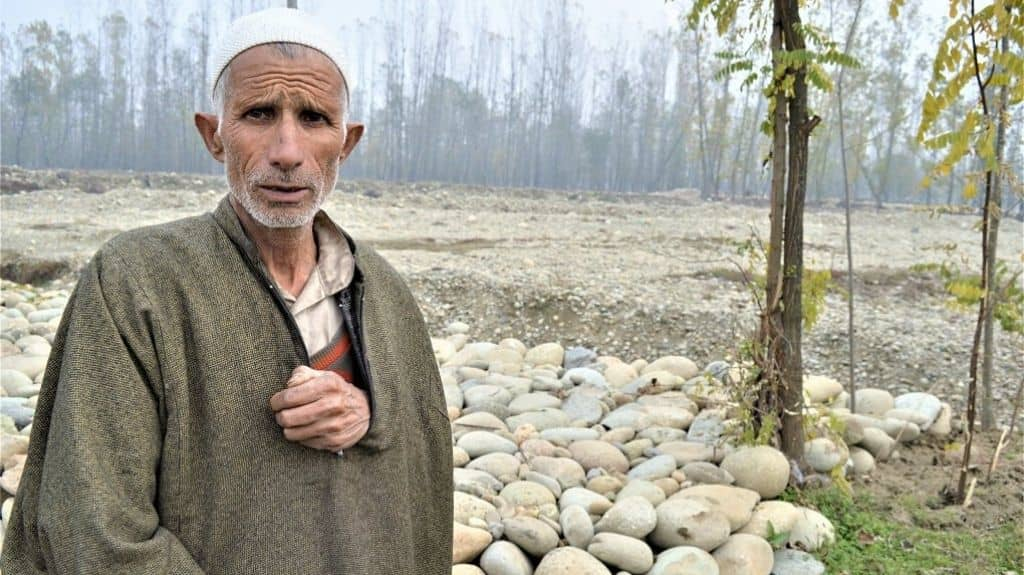 A man standing on the bank of a tributary of Jhelum in south Kashmir, Vishu. In autumn and winters, Jhelum's tributaries have extremely low flows. Photo credit: Athar Parvaiz.
