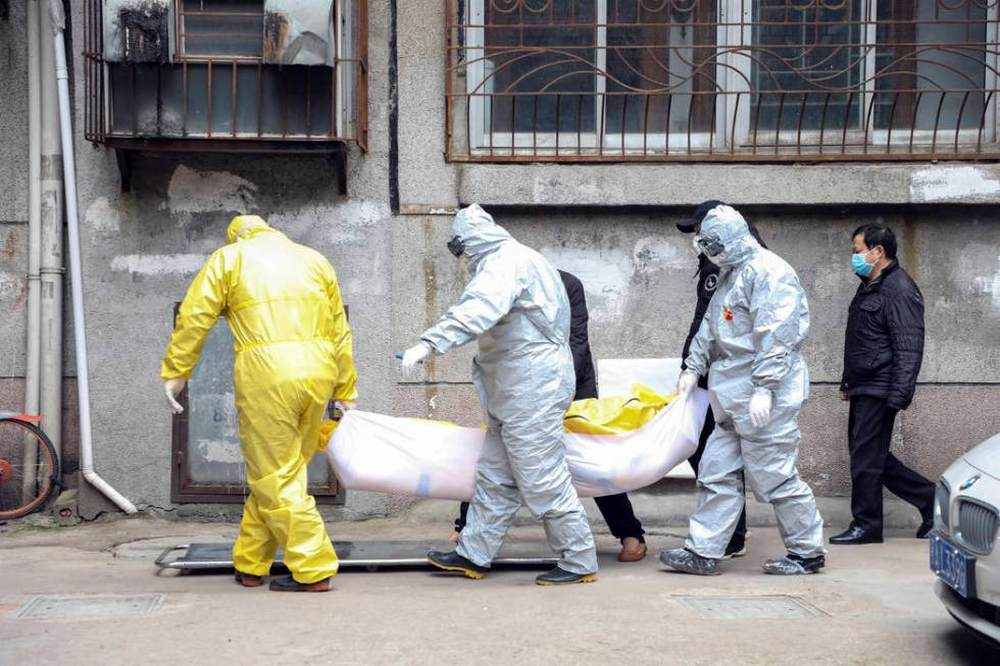 Funeral home workers remove the body of a person suspect to have died from a virus outbreak from a residential building in Wuhan in central China's Hubei Province. Image credit: AP