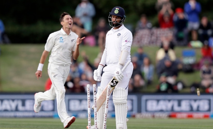 India's Cheteshwar Pujari, centre, walks from the field after he was out bowled for 24 by New Zealand's Trent Boult, right, during play on day two of the second Test between New Zealand and India. AP