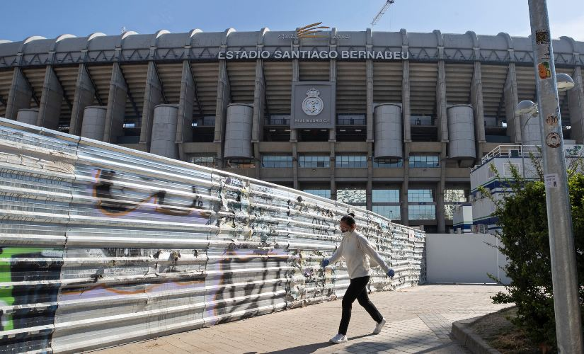 A woman wearing a protective mask walks past Real Madrid's Santiago Bernabeu stadium in Madrid. AP
