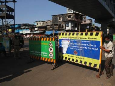 Volunteers put barricades on a road in Dharavi in Mumbai. AP