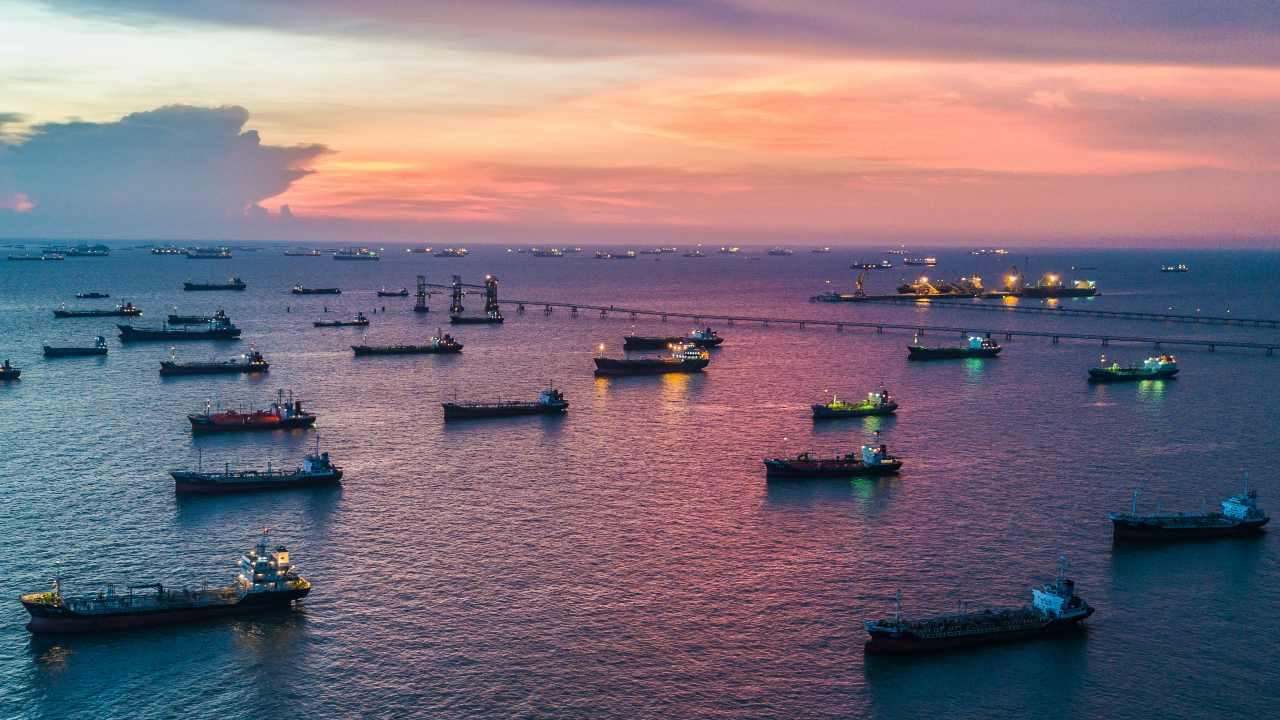 Oil tankers load up in a port at twilight. Avigator Fortuner/Shutterstock
