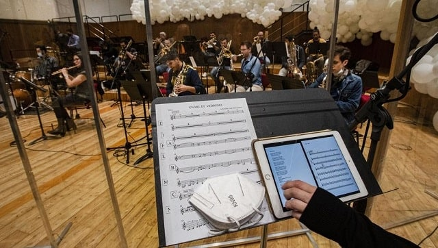 Giuseppe Verdi jazz orchestra musicians and singers play their instruments behind a transparent panel. Image via The Associated Press/Antonio Calanni