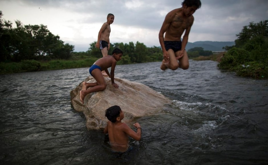Young Honudran migrants played in the waters of the river in Mexico as the caravan of immigrants halted here before embarking upon the nearly 1000 mile march to the United States border. The Associated Press/ Rodrigo Abd