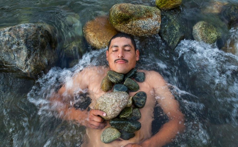 Melvin Marquez from Honduras, relaxes while having a bath in a river in Mexico on Thursday, 25 October, 2018. The Associated Press/ Rodrigo Abd