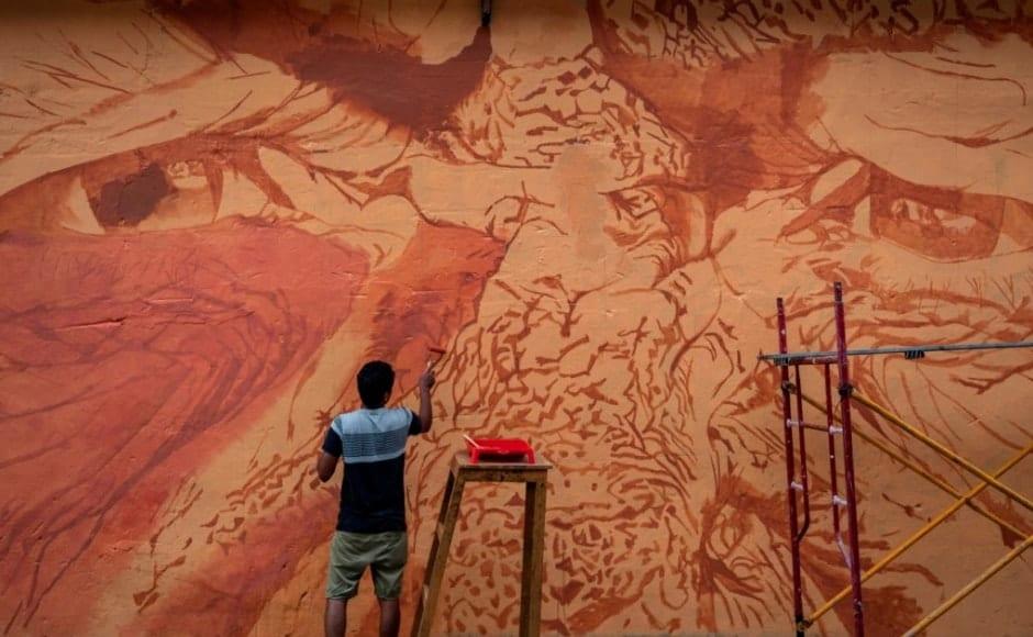 The Maharashtrian artist, Parag Sonarghare, painting the picture of 'Eyes' that banks on realism on the walls near Fadi Auditorium on Bazaar road. Image via Kochi-Muziris Biennale