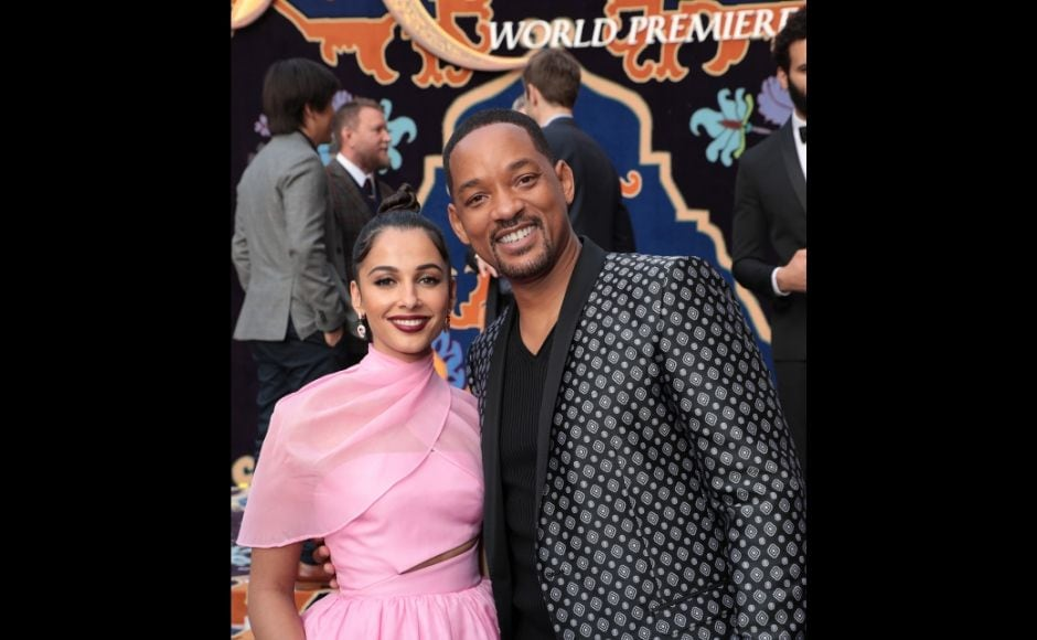Naomi Scott (left) wore a baby pink outfit which the actress teamed with a top-knot. Here, she is seen with Will Smith