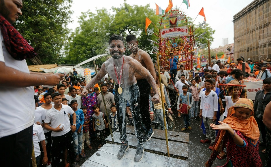Processions similar to the Jagannath Yatra in Puri are held in different parts of India such as Ahmedabad and Kolkata, on the same day. In the above image, a man pours milk on a bodybuilder as they participate at an annual Rath Yatra in Ahmadabad. AP