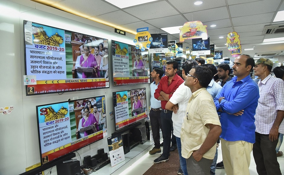 People gather in a shop to watch the live telecast of the Union Budget. Tabling the Modi 2.0 government's maiden budget, Sitharaman said that steps were taken to boost infrastructure in sectors like roads, waterways, metro, and rail. She also emphasised on the measures for a self-reliant aviation industry. PTI
