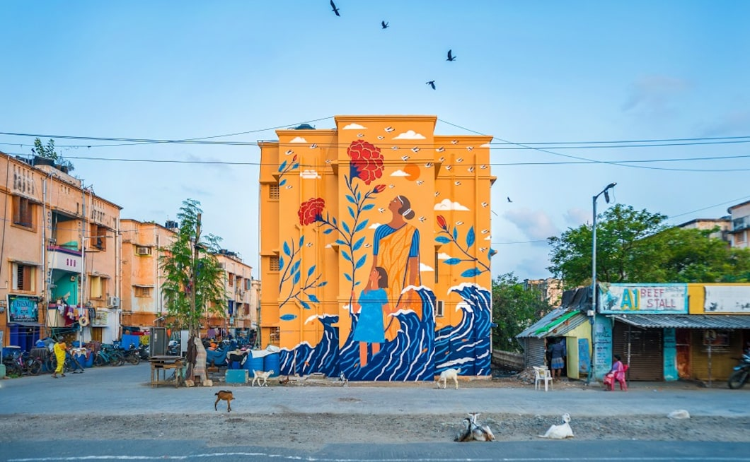 The mural (as shown above) titled 'Harbouring Hope' by artist Kashmira Sarode has been created as an ensemble of hope in the midst of displacement and migration. It is dedicated to inhabitants of the area who had to move from the coast to Kannagi Nagar after the devastating tsunami of 2004. Sarode's mother-daughter duo, placed amidst the waves is shown looking upwards and surrounded by iris flowers – symbolizing the essence of hope in possible traumatic situations.